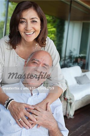 Smiling couple hugging on patio Stock Photo - Premium Royalty-Free, Image code: 635-05651759