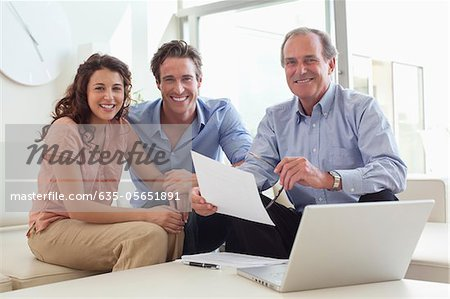 Couple sitting on sofa with financial advisor Stock Photo - Premium Royalty-Free, Image code: 635-05651891