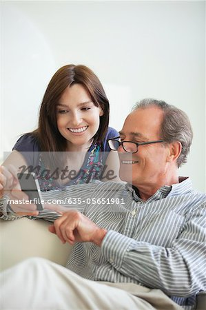 Father showing cell phone to daughter Stock Photo - Premium Royalty-Free, Image code: 635-05651901