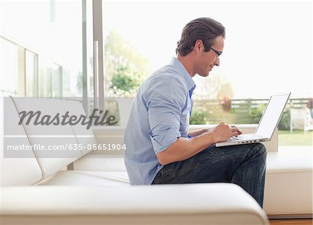 Man sitting on sofa using laptop