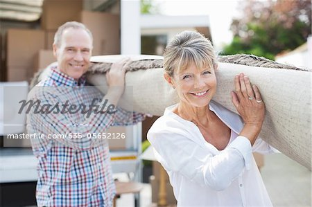 Couple carrying rug together Stock Photo - Premium Royalty-Free, Image code: 635-05652126