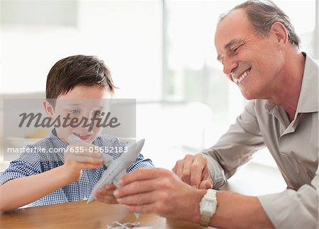 Grandfather and grandson assembling airplane model Stock Photo - Premium Royalty-Free, Image code: 635-05652183