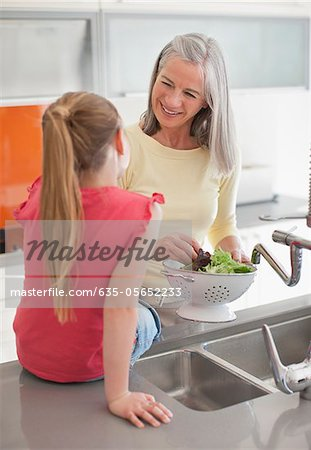 Granddaughter watching grandmother rinsing lettuce Stock Photo - Premium Royalty-Free, Image code: 635-05652233