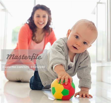 Mother watching baby playing with ball Stock Photo - Premium Royalty-Free, Image code: 635-05652240