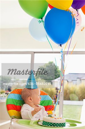 Baby in high chair with birthday cake and balloons Stock Photo - Premium Royalty-Free, Code: 635-05652281