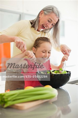 Grandmother and granddaughter preparing salad together Stock Photo - Premium Royalty-Free, Image code: 635-05652284