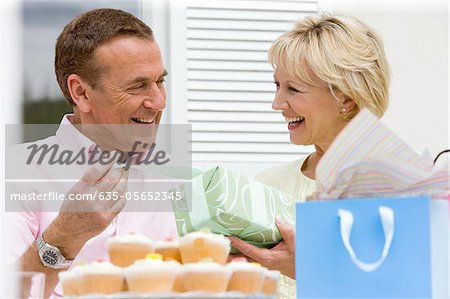 Wife giving birthday gift to husband Stock Photo - Premium Royalty-Free, Image code: 635-05652345