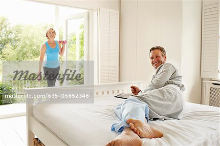Husband on bed watching wife exercising Stock Photo - Premium Royalty-Free, Image code: 635-05652346