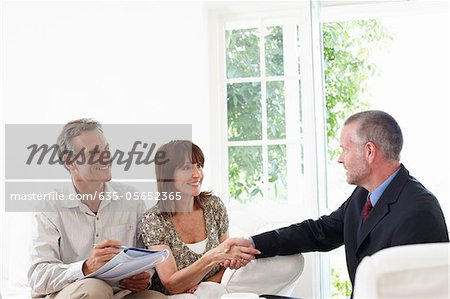Couple shaking hands with financial advisor Stock Photo - Premium Royalty-Free, Image code: 635-05652365