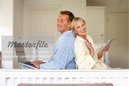 Couple in bedroom using laptop and digital tablet Stock Photo - Premium Royalty-Free, Image code: 635-05652367