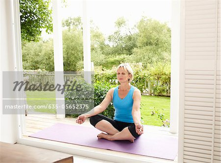 Woman practicing yoga on porch Stock Photo - Premium Royalty-Free, Image code: 635-05652375