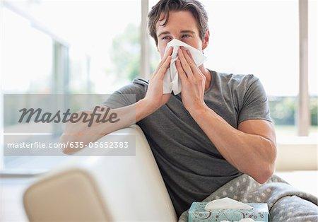 Sick man blowing his nose Stock Photo - Premium Royalty-Free, Image code: 635-05652383