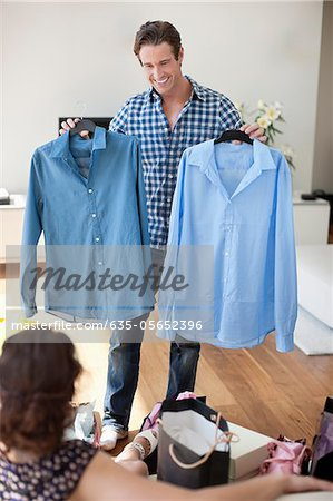 Man showing new shirts to wife Stock Photo - Premium Royalty-Free, Image code: 635-05652396