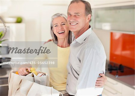 Smiling couple in kitchen with reusable grocery bags Stock Photo - Premium Royalty-Free, Image code: 635-05652398