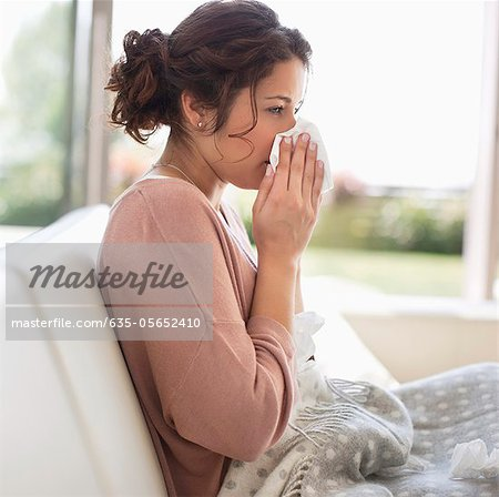 Sick woman blowing her nose Stock Photo - Premium Royalty-Free, Image code: 635-05652410