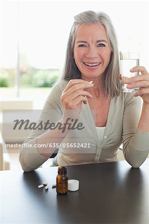 Smiling woman holding glass of water and taking pills Stock Photo - Premium Royalty-Free, Image code: 635-05652421