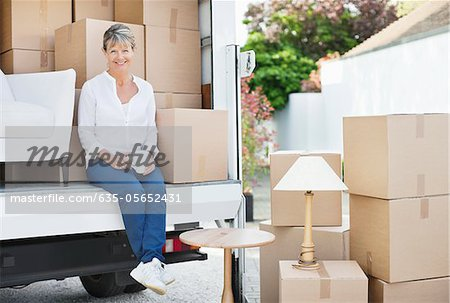 Woman drinking coffee on back of moving van Stock Photo - Premium Royalty-Free, Image code: 635-05652431