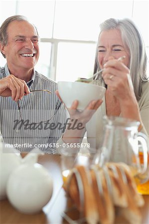 Senior couple laughing at breakfast Stock Photo - Premium Royalty-Free, Image code: 635-05655678