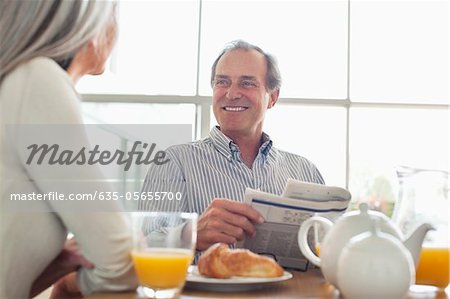 Smiling senior couple at breakfast table Stock Photo - Premium Royalty-Free, Image code: 635-05655700