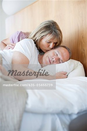 Senior woman kissing man asleep in bed Stock Photo - Premium Royalty-Free, Image code: 635-05655739