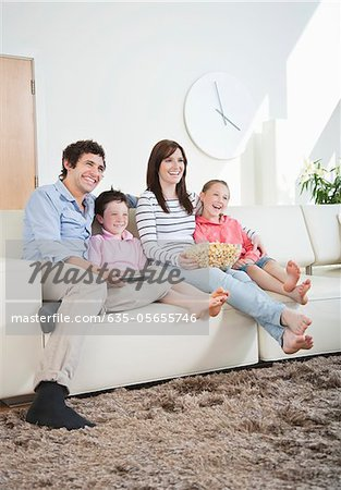 Smiling family watching TV on sofa Stock Photo - Premium Royalty-Free, Image code: 635-05655746