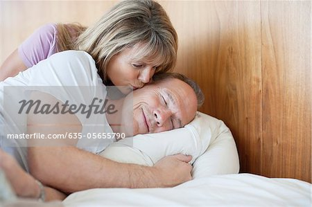 Senior woman kissing man on cheek in bed Stock Photo - Premium Royalty-Free, Image code: 635-05655790