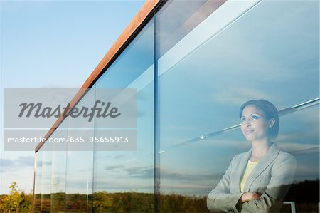 Pensive businesswoman with arms crossed in office window Stock Photo - Premium Royalty-Free, Image code: 635-05655913