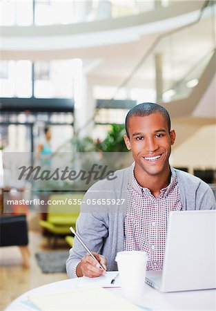 Portrait of confident businessman using laptop and writing on notepad in office Stock Photo - Premium Royalty-Free, Image code: 635-05655927
