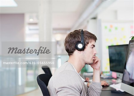 Businessman with headphones working at computer in office