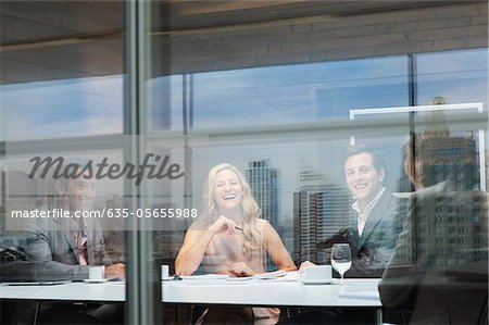 Smiling business people meeting at conference room table