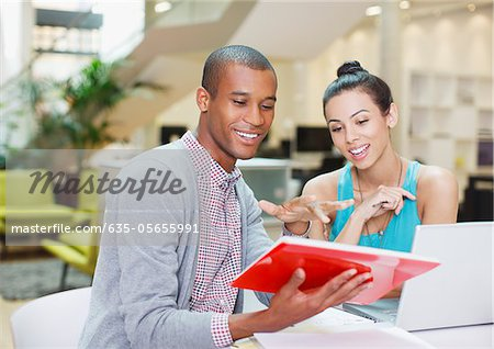 Businessman and businesswoman with laptop and digital tablet in office Stock Photo - Premium Royalty-Free, Image code: 635-05655991