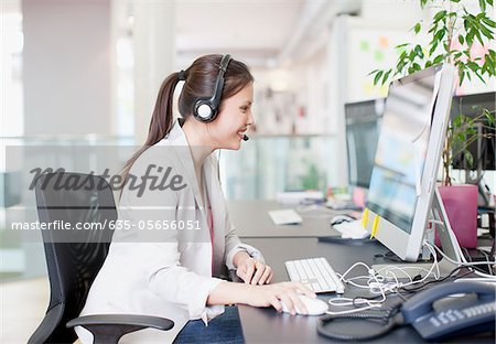 Businesswoman with headset using computer in office