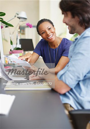 Businessman and businesswoman discussing paperwork in office