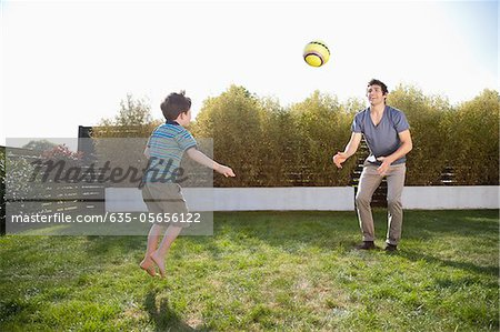 Father and son playing soccer in backyard Stock Photo - Premium Royalty-Free, Image code: 635-05656122