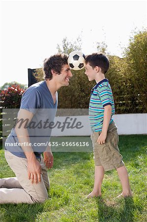 Soccer ball between father and son in backyard Stock Photo - Premium Royalty-Free, Image code: 635-05656136