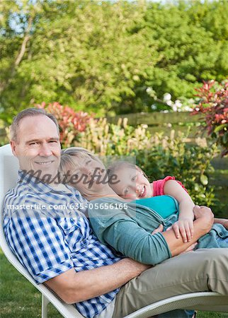 Portrait of smiling grandparents with granddaughter on lounge chair in garden Stock Photo - Premium Royalty-Free, Image code: 635-05656165