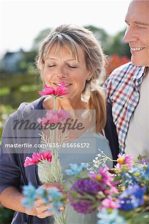 Senior couple smelling flowers in garden Stock Photo - Premium Royalty-Free, Image code: 635-05656172