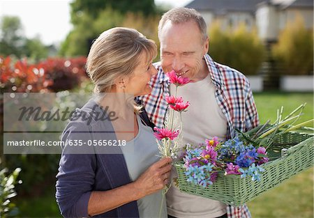 Senior couple smelling flowers in garden Stock Photo - Premium Royalty-Free, Image code: 635-05656218
