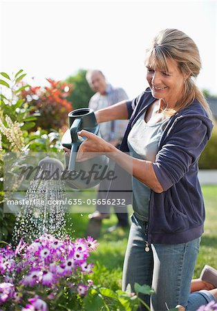 Senior woman watering flowers in garden with watering can Stock Photo - Premium Royalty-Free, Image code: 635-05656232