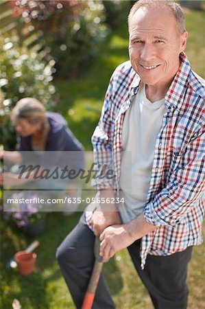 Portrait of smiling senior man working in sunny garden Stock Photo - Premium Royalty-Free, Image code: 635-05656234