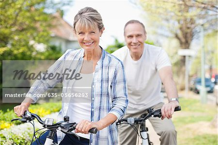 Portrait of smiling senior couple on bicycles Stock Photo - Premium Royalty-Free, Image code: 635-05656293
