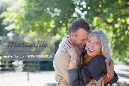 Portrait of smiling couple hugging in sunny park Stock Photo - Premium Royalty-Free, Image code: 635-05656316