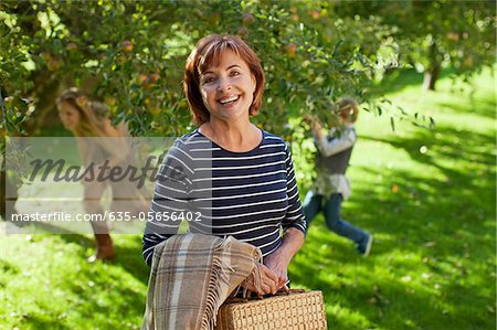 Portrait of smiling woman with blanket and bag in apple orchard Stock Photo - Premium Royalty-Free, Image code: 635-05656402