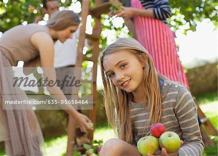 Portrait of smiling girl holding apples in orchard Stock Photo - Premium Royalty-Free, Image code: 635-05656464