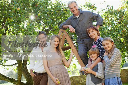 Portrait of smiling multi-generation family on ladder in orchard Stock Photo - Premium Royalty-Free, Image code: 635-05656490