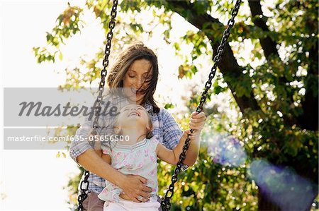 Mother pushing daughter on swing in sunny park Stock Photo - Premium Royalty-Free, Image code: 635-05656500