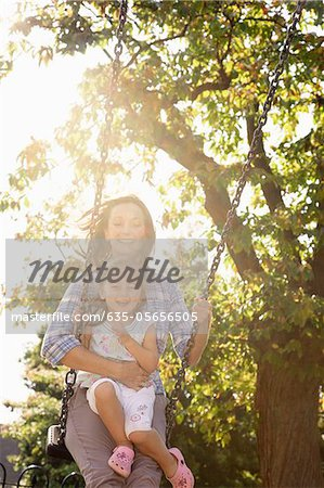 Mother pushing daughter on swing in sunny park Stock Photo - Premium Royalty-Free, Image code: 635-05656505