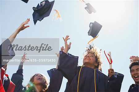 Graduates tossing caps into the air Stock Photo - Premium Royalty-Free, Image code: 635-05971430