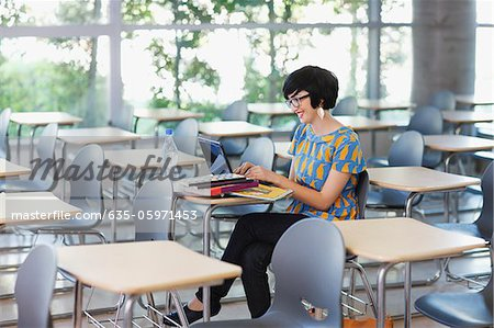 Student using laptop in classroom Stock Photo - Premium Royalty-Free, Image code: 635-05971453