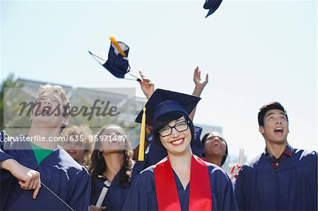 Graduates tossing caps in air outdoors Stock Photo - Premium Royalty-Free, Image code: 635-05971487